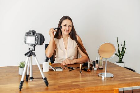 A young attractive woman is recording makeup video tutorials. She demonstrates the technique of applying a bronzer, blush. Concept of online training, online courses, beauty blogging 版權商用圖片