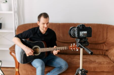 A young man records on the camera acoustic guitar lessons tutorial . Concept of online education, online lessons.