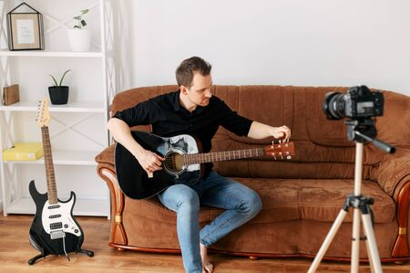 Online guitar lessons for beginners. A young guy with an acoustic guitar records video lessons, guitar tutorial. Online tutor, mentor