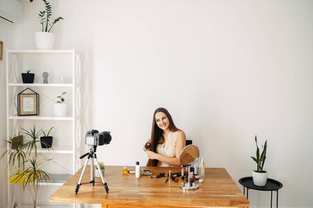 Online learning concept. Beauty industry, beauty blogs. Young woman with long hair records a video on hair care, she combs her hair. She is sitting in a room in front of the camera on a tripod