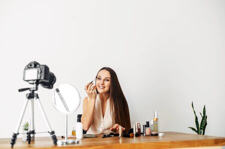 Video recording of eye makeup tutorials. A young woman is putting shadows with a brush on her eyes and recording this on a professional camera. Online training in the beauty industry, beauty blogging.