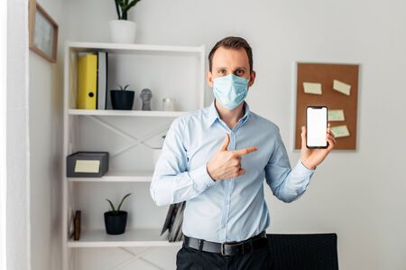 A guy in a formal shirt and a medical maskpoints by a finger on the screen of a smartphone. Work from home during the epidemic, stay home Stock Photo