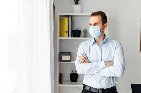 Protect yourself, be careful. A young man in an office in a medical mask stands with his arms crossed on his chest. Pandemic, seasonal diseases
