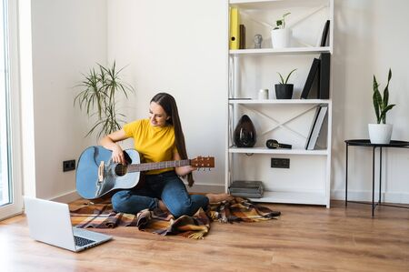 Online training, online classes. A young woman watches video tutorial on guitar playing, she sits on a cozy plaid with a guitar