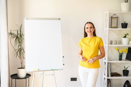Online teacher, tutor, mentor. Confident young woman in yellow t-shirt stands in a bright room near blank flip chart and smiles
