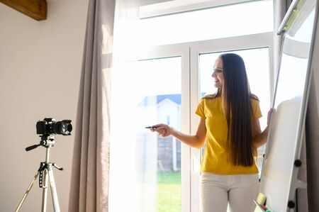 Concept of webinars, online classes, online training. Young woman in casual clothes shows information on a flip chart board and records herself on camera on tripod. Side view