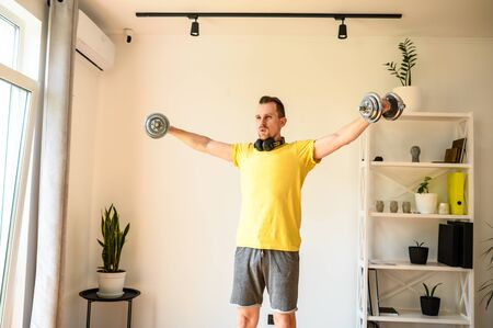 Get in shape yourself. A young guy in sport wear is training at home, he arm and shoulder exercise with iron dumbbells. Concept of healthlife, sport, selfdissipline