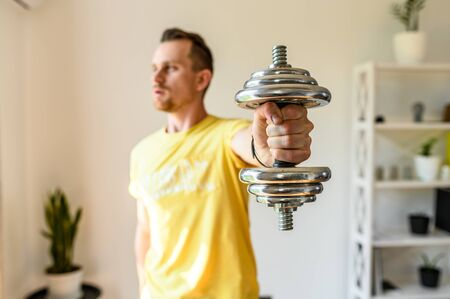 Make your shape better. Put yourself in order by the summer. The guy holds an iron dumbbell in his hand, he demonstrates it to the camera. The concept of a healthy lifestyle and strength workout at home