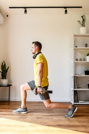 Do yourself better. Young active guy doing lower body workout at home. He doing lunges with dumbbells. The concept of a healthy lifestyle, self-discipline, sporty style