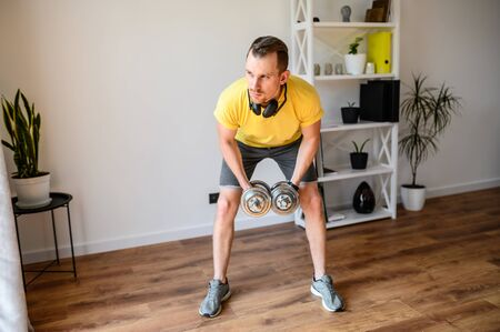 Stay home. A guy has upper body workout at home. He is doing exercises for arms and shoulders with iron dumbbells