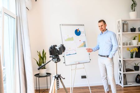 Educational video blogging. A young intelligent guy in a smart casual wear records a video on a camera about the state of the economy in the world, he stands near a flipchart with a graph