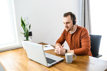 The guy uses hands-free headsets to work from home. He sits at a table with a laptop and speaks online. Remote work concept