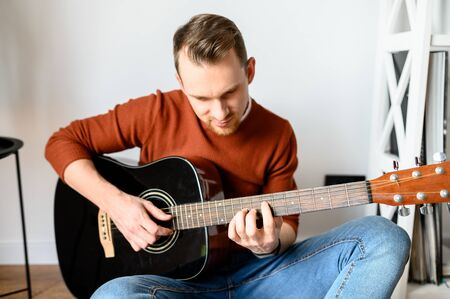 Stay home. A guy spends his leisure time at home playing music. He is sitting on a cozy plaid with an acoustic guitar in his hands. Archivio Fotografico