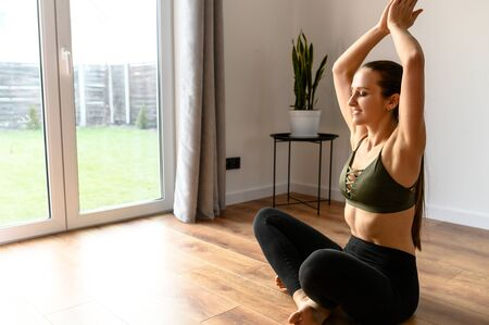 Morning meditation, a good start to the day with yoga. Slender fit girl meditates at home in a easy pose. Healthy lifestyle concept