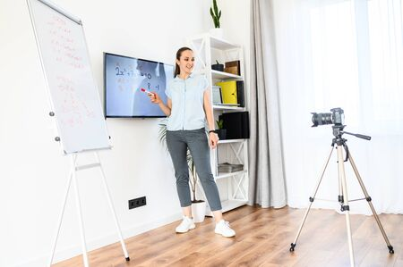 A woman is recording tutorial video at home, uses flip chart and monitor. Camera on tripod in front of woman. Online study concept