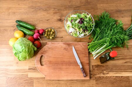 Cooking salad at home. Cutting board with a knife on it, fresh vegetables and greens on the table near. Healthy food concept. Flat lay