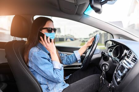 A young woman in a medical mask and in sunglasses is talking on the phone in a car. Coronavirus pandemia, epidemia covid-19 Banque d'images