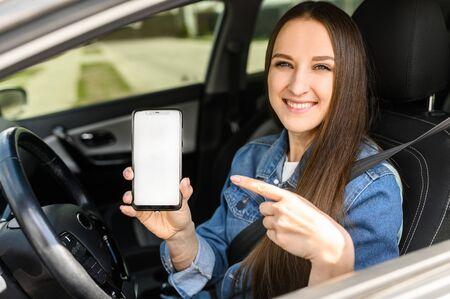 A young beautiful woman driving a car, she points to blank phone screen and smiles. Mobile apps for driver. Outside view Banco de Imagens