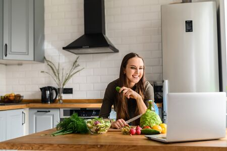 A young woman cooks in the kitchen and looks with interest at the laptop screen. Woman prepare salad, vegetables on the table Stock Photo