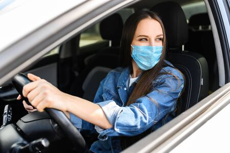 Protective measures in a car during pandemia, epidemia. A young woman in medical mask is driving a car