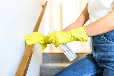 Close-up picture of hands in yellow protective rubber gloves is cleaning the railing on the stairs at home. House cleaning and disinfection.