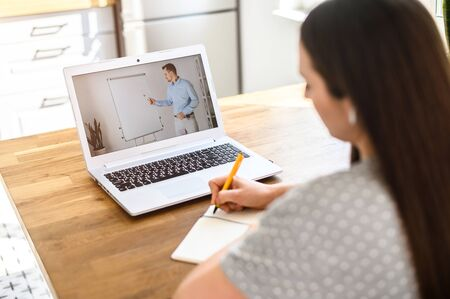 A student studies online. A student girl is watching online classes and writing a syllabus in notebook. Concept of distance study, online learning, webinars. Back view