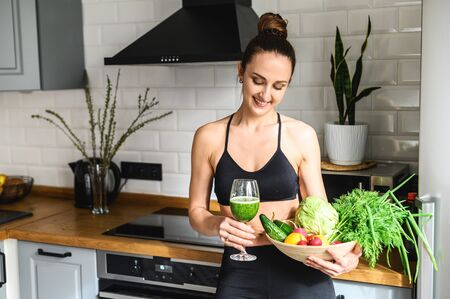 Body detox. Young attractive woman in sportswear in the kitchen with a glass of detox smoothie and a basket of vegetables in her hands Standard-Bild