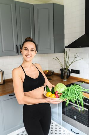 Eat healthy food. Basket of fresh vegetables in hands of young beautiful woman, she looks at camera and smiles in the kitchen Standard-Bild