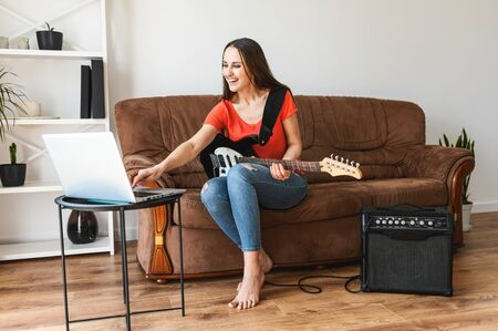 Online guitar lessons. A young woman watches video tutorial how to play on an electric guitar, she sits with a guitar in her hands on a sofa, a combo amplifier is nearby. Online learning concept