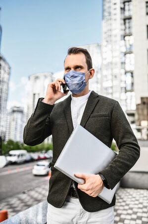 A young businessman in smart casual is walking in cases during pandemic. A guy is in medical mask with laptop talking on the phone outdoors among skyscrapers