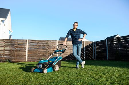 Gardening in the backyard. Young man in a plaid shirt with a push lawn mower on the green grass Archivio Fotografico