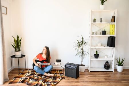 A girl spends home leisure playing an electric guitar. Hobby concept, talent