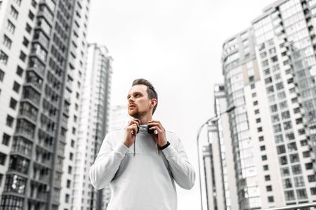 Take a break at workout. Close-up portrait of young man in sports clothing with headphones stand while exercising outside Фото со стока