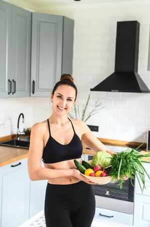 Healthy lifestyle concept. Young sporty woman in the kitchen with a basket of fresh vegetables smiling Standard-Bild