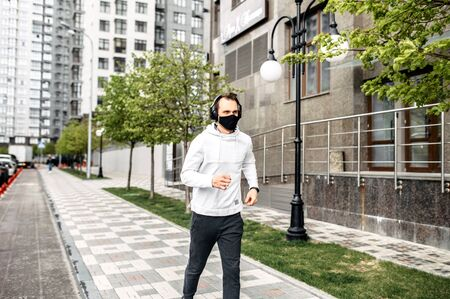 Keep fit during quarantine. A young guy runs in a mask in a cityscape, high-rise buildings on the background. Healthy lifestyle concept Фото со стока