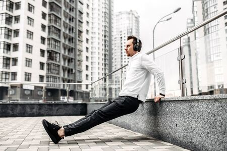 Workout outdoors. A young man in sportswear is warming up around high-rise buildings