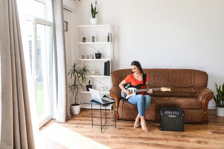 Online learning concept. Young woman watching video tutorials and learning to play the electric guitar, uses a combo amplifier