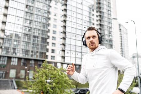 Workout outdoors. Young athletic guy in sportswear with headphones runs in an urban landscape