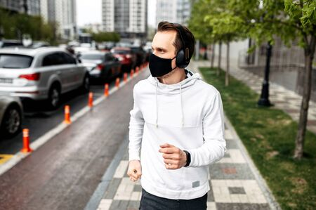 Get in shape during quarantine. Young man in sportswear with a medical mask on his face runs outdoors