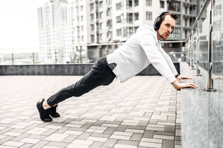 Workout outdoors. A young man in sportswear is push-ups around high-rise buildings