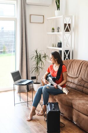 A young woman spends home leisure learning to play an electric guitar. She sits on a sofa and watching on laptop online classes how to play guitar, the guitar is connected to a combo amplifier