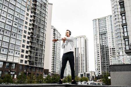 Young man does stretching while exercising outdoors. Urban landscape on background Фото со стока