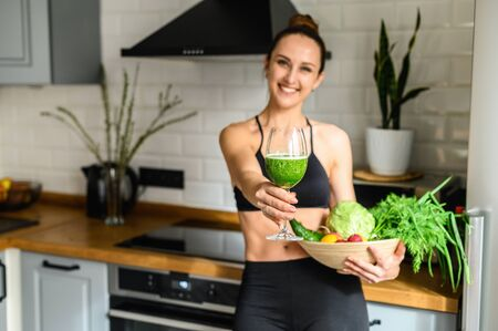 Vegetable smoothie detox in the hands of a young woman, she is in sportswear in the kitchen