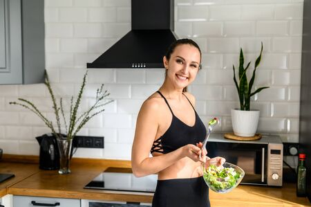 Keep yourself fit. Young woman in sportswear in the kitchen with a bowl of salad in her hands