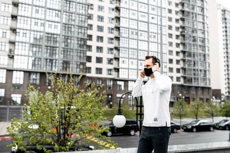 Sports lifestyle. Young athletic man in sportswear in a medical mask with headphones among city skyscrapers