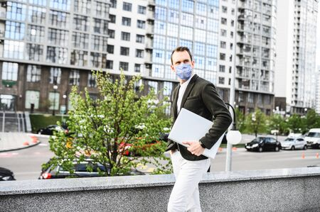 A young businessman in smart casual is walking in cases during pandemic. A guy is in medical mask with laptop outdoors among skyscrapers