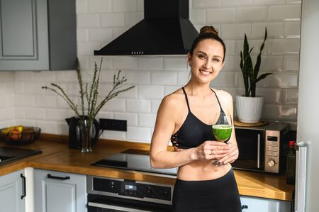 A glass of vegetable smoothie in the hands of a young healthy woman, she is in sportswear standing in the kitchen and smiling Фото со стока