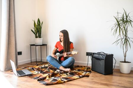 Hobbies and leisure activities during quarantine. Online training, classes. A young woman watches a video lesson on playing the electric guitar, she sits on a cozy plaid with a guitar, combo amp near