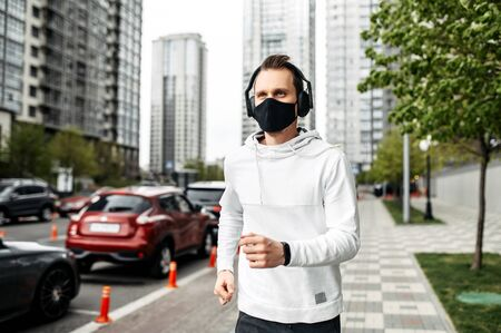 Keep in shape during quarantine. A young man in sports clothing is running in the city outside Фото со стока