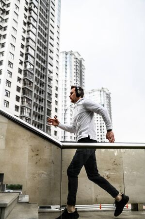 Healthy habits. Full length of young man in sports clothing is running up stairs while exercising outside